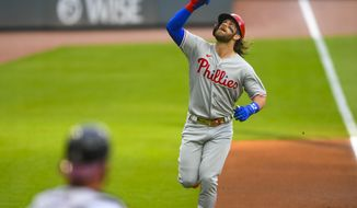 Philadelphia Phillies' Bryce Harper reacts as he approaches home plate after hitting a two-run home run against the Atlanta Braves during the first inning of a baseball game Saturday, Aug. 22, 2020, in Atlanta. (AP Photo/John Amis)
