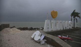 Remnants of city sign lay on the beach, damaged by Tropical Storm Laura in Salinas, Puerto Rico, Saturday, Aug. 22, 2020. Laura began flinging rain across Puerto Rico and the Virgin Islands on Saturday morning and was expected to drench the Dominican Republic, Haiti and parts of Cuba during the day on its westward course. (AP Photo/Carlos Giusti)