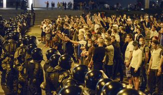 FILE - In this file photo taken on Sunday, Aug. 9, 2020, people argue with police during a rally after the Belarusian presidential election in Minsk, Belarus. Police and protesters clashed in Belarus' capital and the major city of Brest on Sunday after the presidential election in which the authoritarian leader who has ruled for a quarter-century sought a sixth term in office. (AP Photo, File)