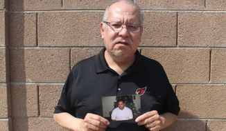 Auska Mitchell holds a photograph of his nephew, Lezmond Mitchell, on Friday, Aug. 21, 2020 in Goodyear, Ariz. Lezmond Mitchell is scheduled to be executed Wednesday, Aug. 26, and the Navajo government is pushing to spare his life on the basis of cultural beliefs and sovereignty. (AP Photo/Jonathan J. Cooper)