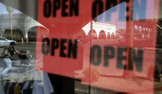 FILE - In this June 30, 2020, photo, a man passes a clothing shop with open signs in the window in Calexico, Calif. Records obtained by The Associated Press show governors working closely with business interests as they weighed when and how to reopen their economies during the coronavirus pandemic. (AP Photo/Gregory Bull, File)