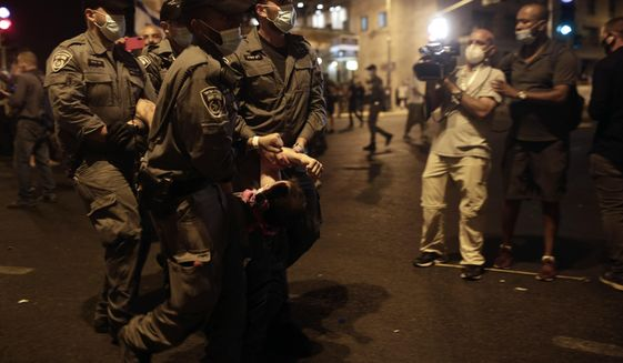 Police carry a protester away as they clear the square outside of Prime Minister Benjamin Netanyahu's residence in Jerusalem, late Saturday, Aug. 22, 2020. (AP Photo/Maya Alleruzzo)