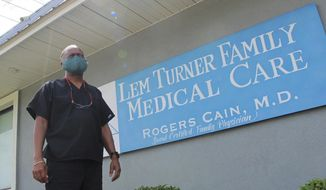 Dr. Rogers Cain stands outside his family medical clinic in north Jacksonville, Fla., on Thursday, July 30, 2020. Over the past two decades, he has seen the county health department gutted of money and people, hampering Duval's ability to respond to outbreaks, including a small cluster of tuberculosis cases in 2012. (AP Photo/Jason Dearen)