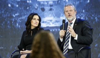 """This Wednesday, Nov. 28, 2018, file photo shows the Rev. Jerry Falwell Jr., right, and his wife during after a town hall at a convocation at Liberty University in Lynchburg, Va. Falwell Jr. says he is seeking help for the """"emotional toll"""" from an affair his wife had with a man who he says later threatened his family. (AP Photo/Steve Helber)"""