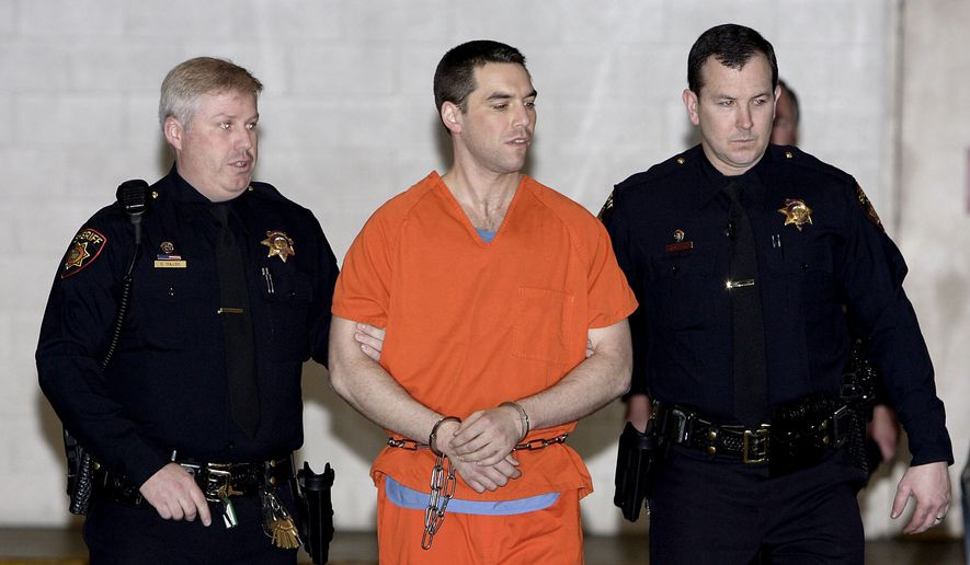 In this March 17, 2005, file photo, Scott Peterson is escorted by two San Mateo County Sheriff deputies as he is walked from the jail to a waiting van in Redwood City, Calif. The California Supreme Court has overturned the 2005 death sentence for Peterson in the slaying of his pregnant wife. The court says prosecutors may try again for the same sentence if they wish in the high-profile case. It upheld his 2004 conviction of murdering Laci Peterson, who was eight months pregnant with their unborn son. (AP Photo/Justin Sullivan, Pool, File)