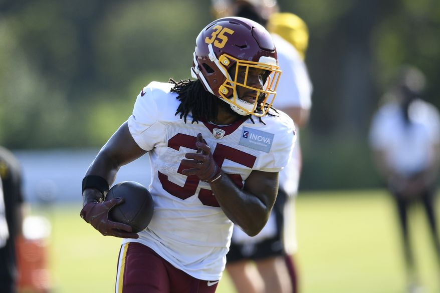 Washington running back Bryce Love (35) runs with the ball during practice at the team's NFL football training facility, Monday, Aug. 24, 2020, in Ashburn, Va. (AP Photo/Nick Wass)
