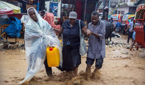 Street vendors wade a flooded street during the passing of Tropical Storm Laura in Port-au-Prince, Haiti, Sunday, Aug. 23, 2020. Laura battered the Dominican Republic and Haiti and is heading for a possible hit on the Louisiana coast at or close to hurricane force as a hurricane, along with Tropical Storm Marco. (AP Photo/Dieu Nalio Chery)