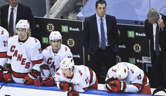 Carolina Hurricanes head coach Rod Brind'Amour, back center, looks on as players on the bench hang their heads after being eliminated by the Boston Bruins in an NHL Eastern Conference Stanley Cup playoff hockey game in Toronto, Ontario, on Wednesday, Aug. 19, 2020. (Nathan Denette/The Canadian Press via AP)