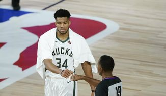 Milwaukee Bucks' Giannis Antetokounmpo (34) fist bumps referee James Capers (19) after an NBA basketball first round playoff game against the Orlando Magic Monday, Aug. 24, 2020, in Lake Buena Vista, Fla. The Bucks won 121-106. (AP Photo/Ashley Landis, Pool)  **FILE**