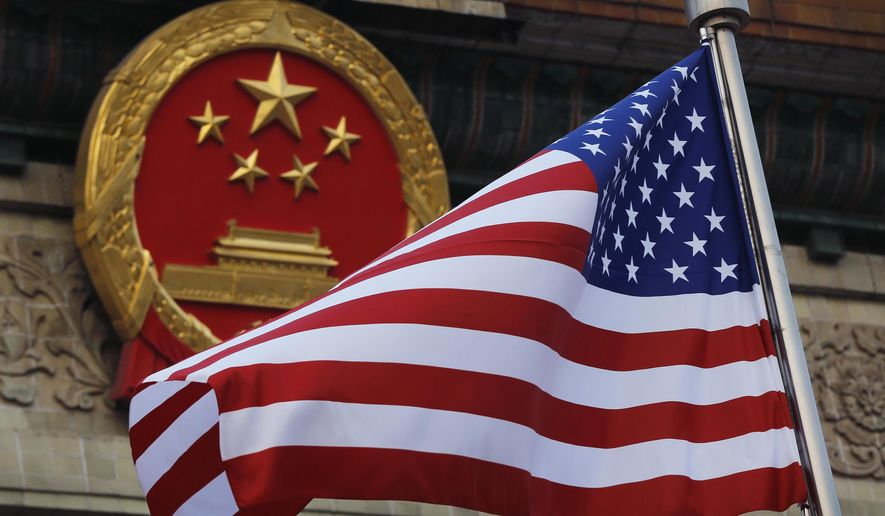 In this Nov. 9, 2017, photo, an American flag is flown next to the Chinese national emblem during a welcome ceremony for visiting U.S. President Donald Trump outside the Great Hall of the People in Beijing. (AP Photo/Andy Wong) **FILE**
