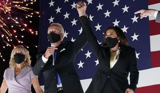 Democratic presidential candidate former Vice President Joe Biden raises his arm with his running mate Sen. Kamala Harris, D-Calif., during the fourth day of the Democratic National Convention, Thursday, Aug. 20, 2020, at the Chase Center in Wilmington, Del. Jill Biden is at left. (AP Photo/Andrew Harnik)
