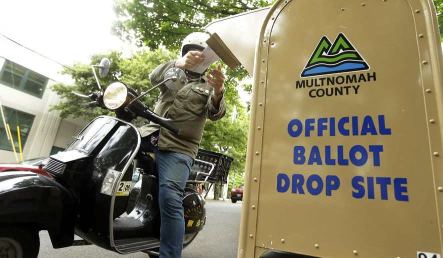 In this May 15, 2018, file photo, a voter drops off his ballot on the day of Oregon's primary election at a drive-by, drop-off station in Portland, Ore. (AP Photo/Don Ryan, File)