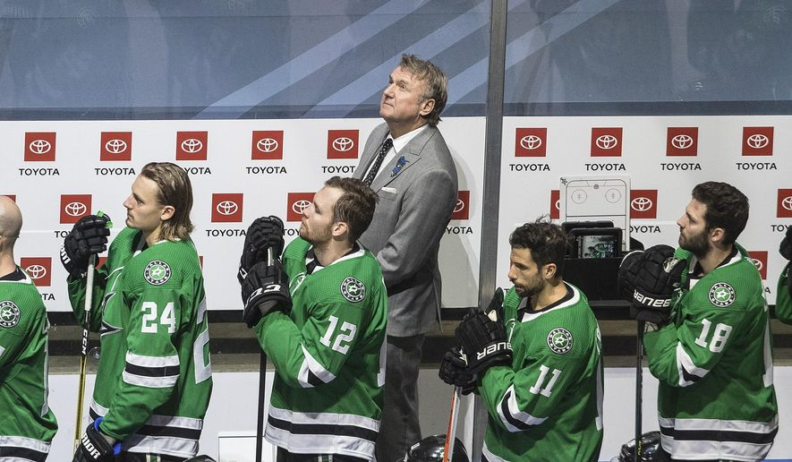 Dallas Stars head coach Rick Bowness looks up to Dale Hawerchuk as he is honored before NHL Western Conference Stanley Cup playoff action against the Calgary Flames, in Edmonton, Alberta, Tuesday, Aug. 18, 2020. (Jason Franson/The Canadian Press via AP)