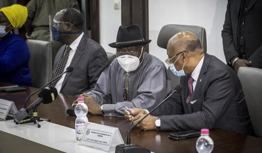Mediator for the West African regional bloc known as ECOWAS and former Nigerian president Goodluck Jonathan, center, speaks with ECOWAS Commission President Jean-Claude Kassi Brou, right, as they meet with representatives of the National Committee for the Salvation of the People at the Ministry of Defense in Bamako, Mali Saturday, Aug. 22, 2020. Top West African officials are arriving in Mali's capital following a coup in the nation this week to meet with the junta leaders and the deposed president in efforts to negotiate a return to civilian rule. (AP Photo)