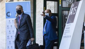 The Syrian Constitutional Committee Co-Chair Hadi al-Bahra, left, wearing face mask as precaution against the spread of the coronavirus as he leaves the building following the announcement of the suspension of the conference due to cases of Covid-19, affecting members of one of the delegations, at the European headquarters of the United Nations in Geneva, Switzerland, Monday, Aug. 24, 2020. (Salvatore Di Nolfi/Keystone via AP)