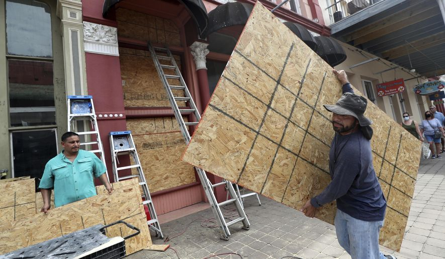 """Cesar Reyes, right, carries a sheet of plywood to cut to size as he and Robert Aparicio, left, and Manuel Sepulveda, not pictured, install window coverings at Strand Brass and Christmas on the Strand, 2115 Strand St., in Galveston on Monday, Aug. 24, 2020. Ginger Herter, who manages the shop, was erring on the side of caution boarding up the storefront as she waits to see what path Tropical Storm Laura will take as it heads toward the Texas and Louisiana coasts. """"I'd rather do this and have to take them down rather than scramble to get them up later in the week,"""" she said. ( Jennifer Reynolds/The Galveston County Daily News via AP)"""