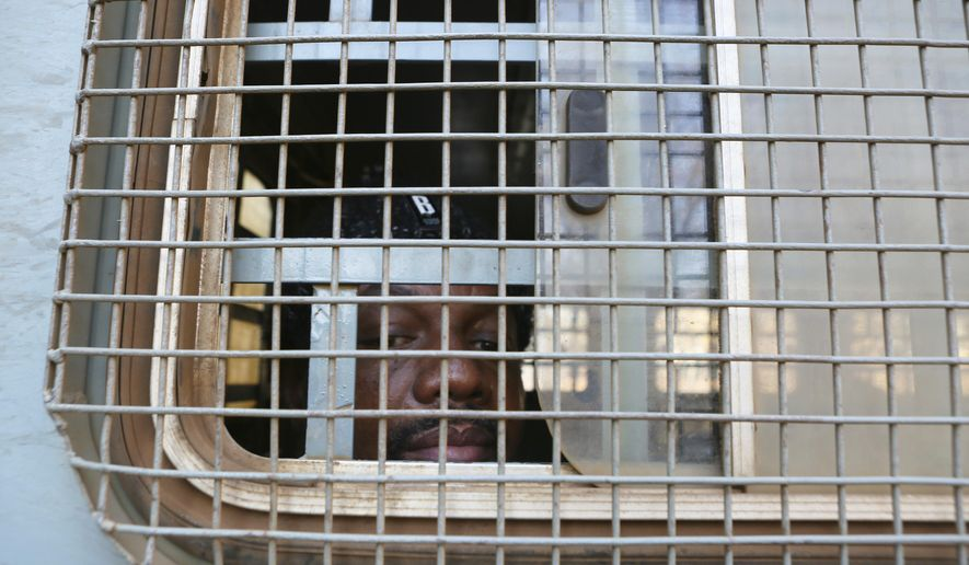 Zimbabwe Journalist Hopwell Chin'ono is seen through the window of a prison truck upon his arrival at the magistrates courts for his bail ruling in Harare, Monday, Aug, 24, 2020. A magistrate has denied bail to Chin'ono saying that they are no new circumstances to warrant bail for the freelance journalist who has been in custody for over a month. Chin'ono is accused of mobilizing anti government protests and is among more than 100 100 government critics who have been arrested in recent months ,according to human rights groups.(AP Photo/Tsvangirayi Mukwazhi)