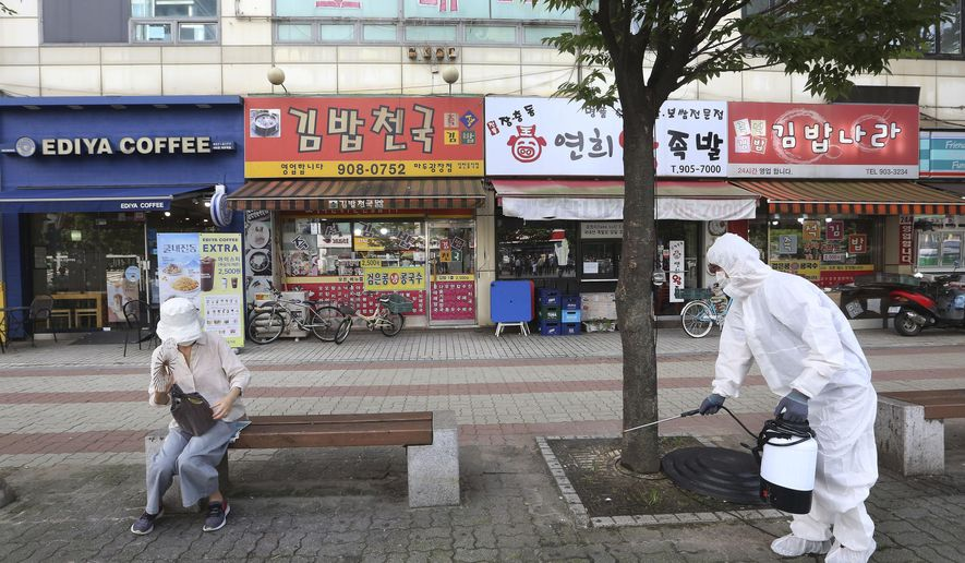 A worker disinfects as a precaution against the coronavirus on a street in Goyang, South Korea, Tuesday, Aug. 25, 2020. South Korea is closing schools and switching back to remote learning in the greater capital area as the country counted its 12th straight day of triple-digit daily increases in coronavirus cases. (AP Photo/Ahn Young-joon)