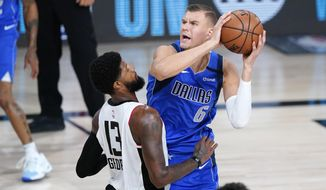 Dallas Mavericks' Kristaps Porzingis (6) is defended by Los Angeles Clippers' Paul George (13) during the first half of an NBA basketball first round playoff game Friday, Aug. 21, 2020, in Lake Buena Vista, Fla. (AP Photo/Ashley Landis, Pool)