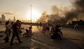 Wounded people are evacuated as smoke rises from a massive explosion in Beirut, Lebanon, Tuesday, Aug. 4, 2020. The massive explosion fueled widespread anger at Lebanon's ruling elite, whose corruption and negligence many blame for the disaster. Yet, three weeks later, the change many hoped for is nowhere in sight and the same politicians are negotiating among themselves over a new government. (AP Photo/Hassan Ammar)