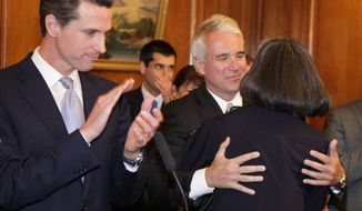 FILE - In this June 17, 2009 file photo, George Gascon, center, San Francisco's new police chief, hugs outgoing chief Heather Fong, right, as then Mayor Gavin Newsom, left, applauds during an introduction and news conference at City Hall in San Francisco. Newsom, now governor of California, on Tuesday, Aug. 25, 2020 endorsed Gascon, in the race for the top prosecutor's job in Los Angeles. Newsom endorsed Gascon in his campaign to unseat District Attorney Jackie Lacey, who is seeking a third term to lead the largest local prosecutor's office in the nation. (AP Photo/Eric Risberg,File)