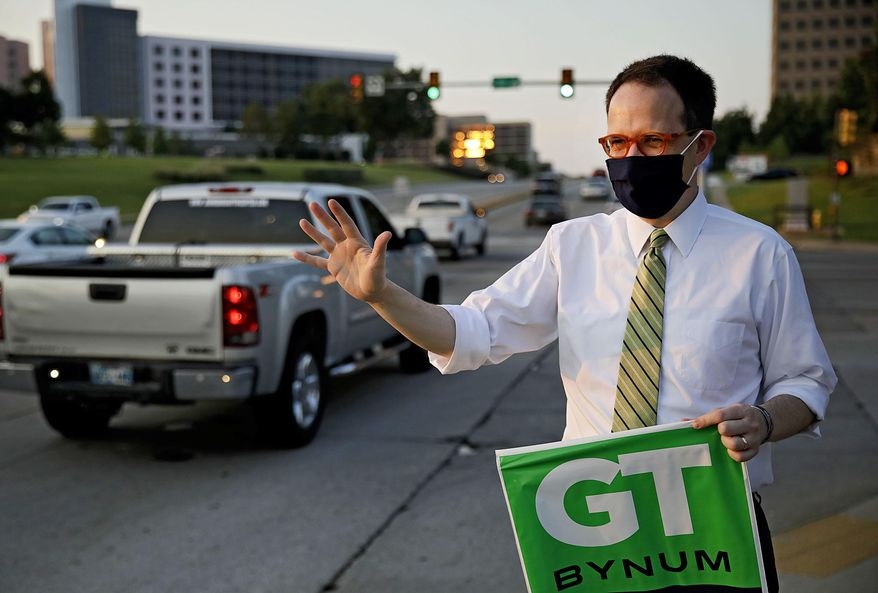 Tulsa Mayor G.T. Bynum waves to motorists at 61st Street and Yale Ave. as he campaigns at sunrise on election day Tuesday, Aug. 25, 2020. (Mike Simons/Tulsa World via AP)
