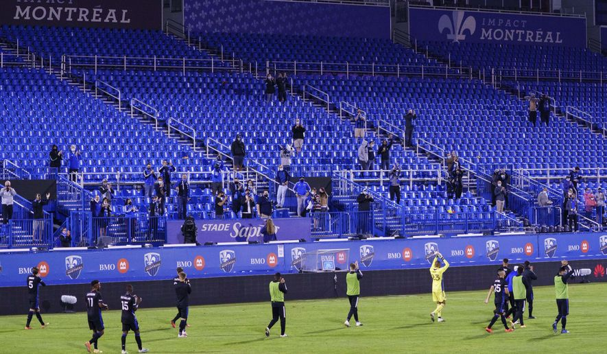 Members of the Montreal Impact salute the crowd following their 2-0 victory over the Vancouver Whitecaps during MLS action in Montreal on Tuesday, Aug. 25, 2020. (Paul Chiasson/The Canadian Press via AP)