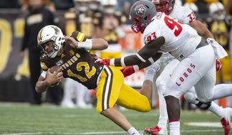 FILE - In this Oct. 19, 2019, file photo, Wyoming quarterback Sean Chambers (12) runs against New Mexico's Nahje Flowers during an NCAA college football game in Laramie, Wy. Family members of Flowers announced Tuesday, Aug. 25, 2020, they will sue New Mexico and the NCAA for his November 2019 death from a self-inflicted gunshot wound. The family says the school did not provide needed mental health treatement. (AP Photo/Michael Smith, File)