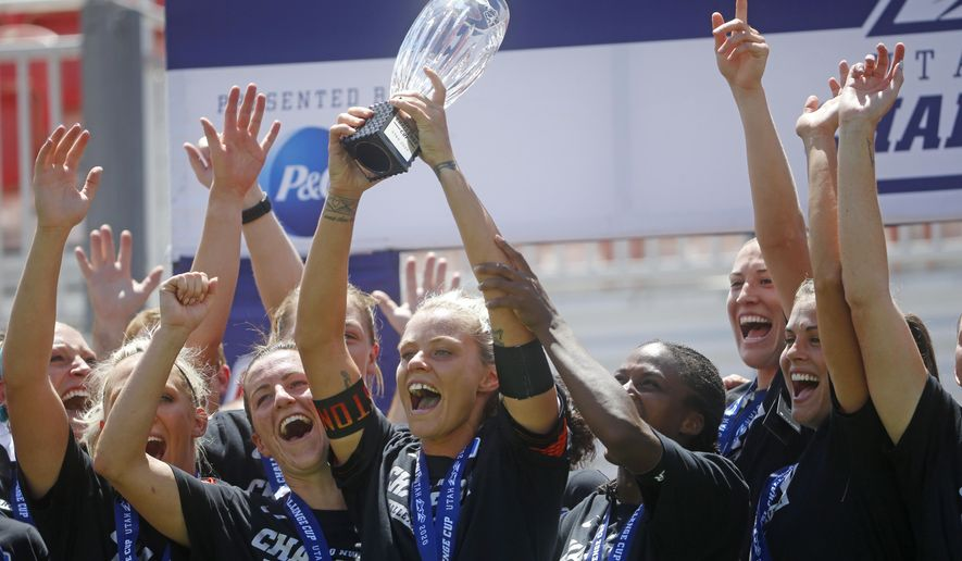Houston Dash forward Rachel Daly holds the trophy alongside teammates while celebrating their NWSL soccer Challenge Cup championship win over the Chicago Red Stars, Sunday, July 26, 2020, in Sandy, Utah. (AP Photo/Rick Bowmer)