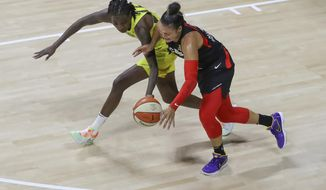 Las Vegas Aces' Kayla McBride, right, has the ball knocked away by Seattle Storm's Natasha Howard during the second half of a WNBA basketball game Saturday, Aug. 22, 2020, in Bradenton, Fla. (AP Photo/Mike Carlson)