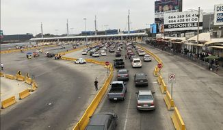 Cars wait in line to enter the United States at San Diego's San Ysidro border crossing, Tuesday, Aug. 25, 2020, in Tijuana, Mexico. A Trump administration crackdown on nonessential travel coming from Mexico amid the coronavirus pandemic has created massive bottlenecks at the border, with drivers reporting waits of up to 10 hours to get into the U.S. (AP Photo/Elliot Spagat)