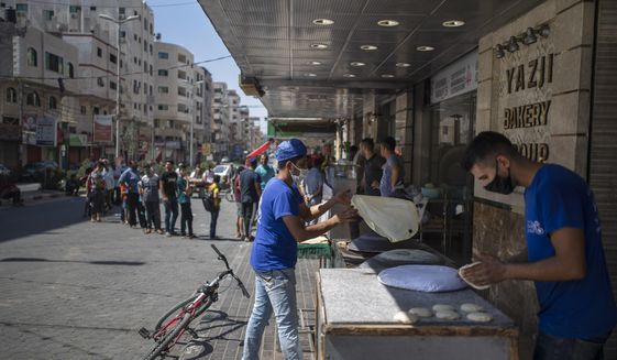 Palestinians line up in front of a bakery to buy bread during a 48 hour lockdown imposed following the discovery of the first coronavirus cases in the Gaza Strip, Tuesday, Aug. 25, 2020. (AP Photo/Khalil Hamra)