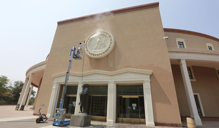 A maintenance worker power-washes the state seal at an entrance of the capitol building on Monday, Aug. 24, 2020, in Santa Fe, New Mexico. The building has been closed to the public since the onset of the coronavirus pandemic. Legislative meetings and gubernatorial addresses are broadcast online. (AP Photo/Cedar Attanasio)