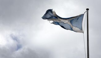 A torn Scottish Saltire flag hangs over the Royal Mile in Edinburgh, Scotland, Friday, Aug, 21, 2020. The handling of the coronavirus pandemic by Scottish leader Nicola Sturgeon has drawn praise, in contrast to the sometimes-chaotic approach of U.K. Prime Minister Boris Johnson. That has catapulted the idea of Scottish independence from the U.K. back up the political agenda. (AP Photo/David Cheskin)