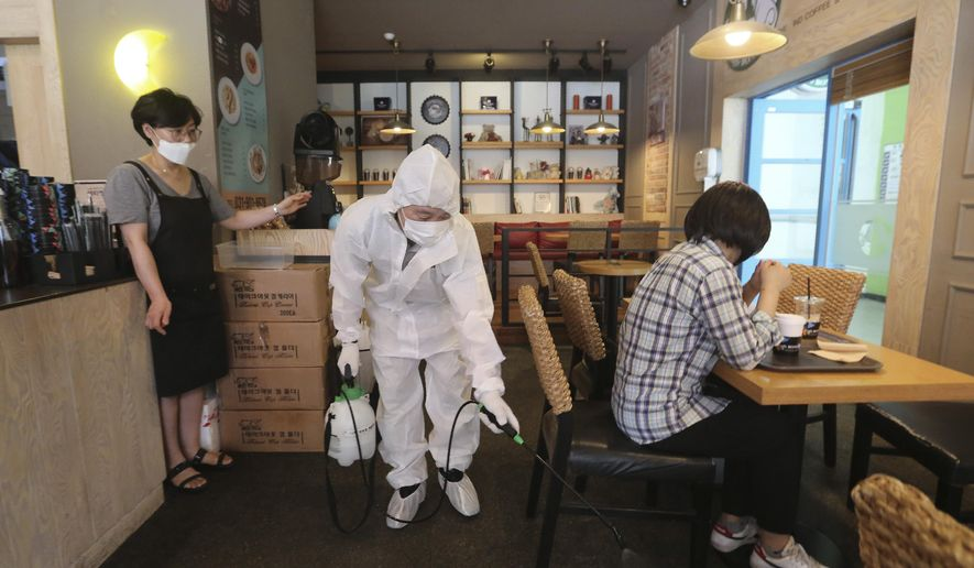 A worker disinfects as a precaution against the coronavirus at a cafe in Goyang, South Korea, Tuesday, Aug. 25, 2020. South Korea is closing schools and switching back to remote learning in the greater capital area as the country counted its 12th straight day of triple-digit daily increases in coronavirus cases. (AP Photo/Ahn Young-joon)