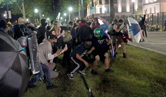 Protesters take cover during clashes with police outside the Kenosha County Courthouse, late Tuesday, Aug. 25, 2020, in Kenosha, Wis. Protests continue following the police shooting of Jacob Blake two days earlier. (AP Photo/David Goldman)