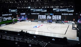 Officials stand beside an empty court at the scheduled start of an NBA basketball first round playoff game between the Milwaukee Bucks and the Orlando Magic, Wednesday, Aug. 26, 2020, in Lake Buena Vista, Fla. The Milwaukee Bucks didn't take the floor in protest against racial injustice and the shooting of Jacob Blake, a Black man, by police in Kenosha, Wisconsin. (AP Photo/Ashley Landis, Pool)