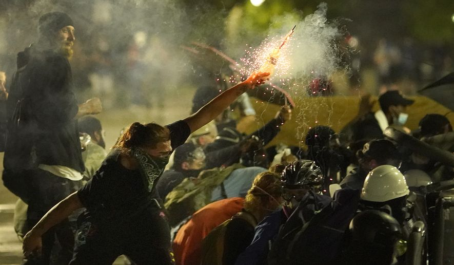A protester launches a projectile toward police during clashes outside the Kenosha County Courthouse, late Tuesday, Aug. 25, 2020, in Kenosha, Wis. Protests continue following the police shooting of Jacob Blake two days earlier. (AP Photo/David Goldman)