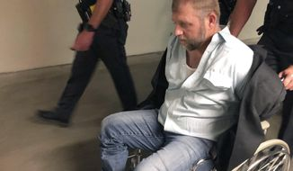 Anti-government activist Ammon Bundy is wheeled from the Idaho Statehouse in Boise, Idaho, on Wednesday, Aug. 26, 2020, following his second arrest for trespassing in two days. Bundy was arrested Tuesday in a committee room and charged with trespassing. (AP Photo/Keith Ridler)