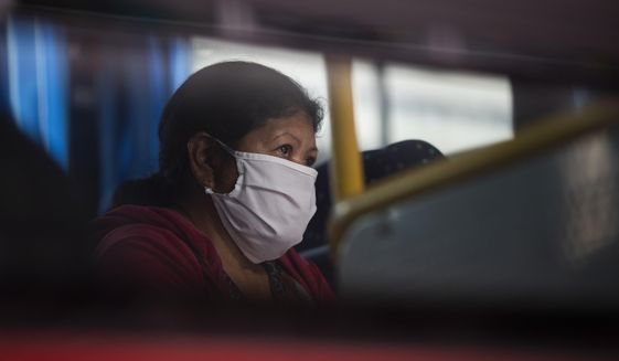 A woman who tested positive for COVID-19 waits  in a bus prior to her admission to a former students residence being used to quarantine asymptomatic patients infected with the new coronavirus in Caracas, Venezuela, Tuesday, Aug 25, 2020. (AP Photo/Ariana Cubillos)