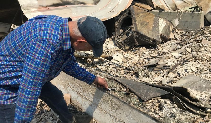 Charles Christianson, a 67-year-old retired school teacher goes through remains at his destroyed home after damage from a wildfire in Guerneville, Calif. on Tuesday, Aug. 25, 2020. (AP Photo/Aron Ranen)