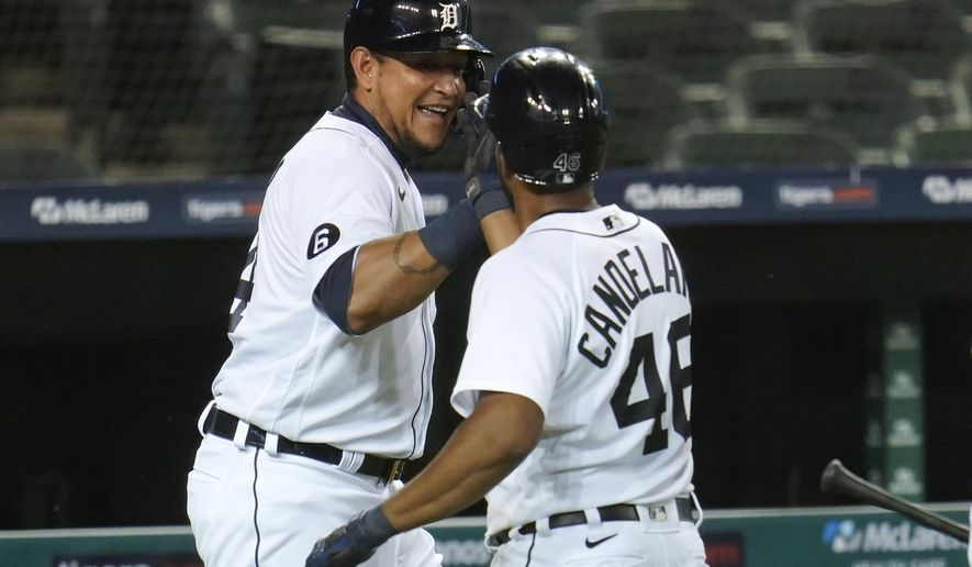 Detroit Tigers' Miguel Cabrera and Jeimer Candelario (46) celebrate scoring on a Niko Goodrum double in the sixth inning of a baseball game against the Chicago Cubs in Detroit, Wednesday, Aug. 26, 2020. (AP Photo/Paul Sancya)
