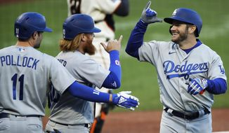 Los Angeles Dodgers' Max Muncy, right, celebrates with Justin Turner, second from left, and A.J. Pollock, left, after hitting a three-run home run off San Francisco Giants' Johnny Cueto in the first inning of a baseball game Tuesday, Aug. 25, 2020, in San Francisco. (AP Photo/Ben Margot)