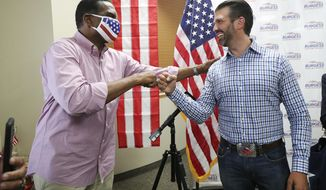 Donald Trump Jr., right, meets with congressional candidate Burgess Owens and volunteers at Colonial Flag in Sandy, Utah, Thursday, July 23, 2020. Owens, a Black conservative running for Congress in Utah, is set to speak at the Republican National Convention on Wednesday, Aug. 26, 2020. (Jeffrey D. Allred/The Deseret News via AP)