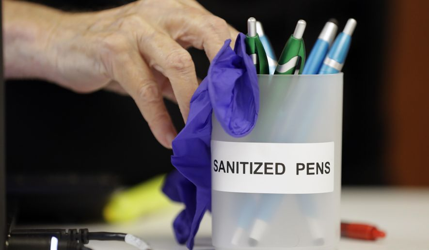 A poll worker pushes a container of sanitized pens to a voter to be used in voting Thursday, Aug. 6, 2020, in Brentwood, Tenn. The state is encouraging voters to wear masks and follow social distancing protocols at the polls. (AP Photo/Mark Humphrey)