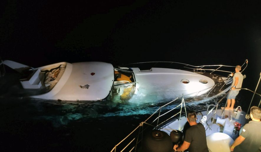 In this photo provided on Wednesday, Aug. 26, 2020 by the Greek Coast Guard, a half-sunken yacht is photographed during a search and rescue operation by the Greek authorities west of the small island of Halki, near Rhodes, southeastern Greece. A total of 96 people were rescued from the sea as the migrants had been travelling in the yacht that was found partially sunk. (Greek Coast Guard via AP)