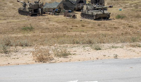 Israeli soldiers sit in a tent next to their mobile artillery units near the border with Lebanon, northern Israel, Wednesday, Aug. 26, 2020. The Israeli military said attack helicopters have struck observation posts of the militant Hezbollah group along the Lebanon border after shots were fired at Israeli troops. Israel has been bracing for a possible attack by Hezbollah since an Israeli airstrike killed a Hezbollah fighter in neighboring Syria last month. (AP Photo/Ariel Schalit)