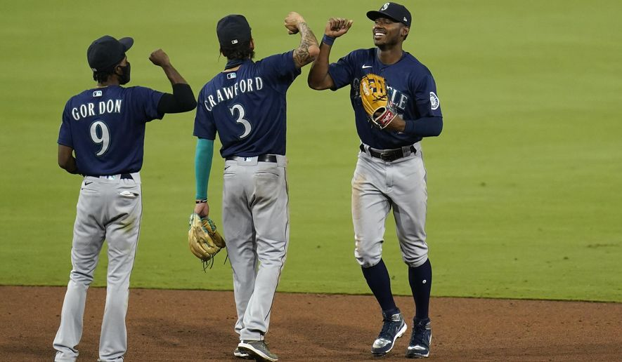 Seattle Mariners center fielder Kyle Lewis, right, celebrates with teammate shortstop J.P. Crawford (3) and second baseman Dee Gordon (9) after the Mariners defeated the San Diego Padres in a baseball game Tuesday, Aug. 25, 2020, in San Diego. (AP Photo/Gregory Bull)
