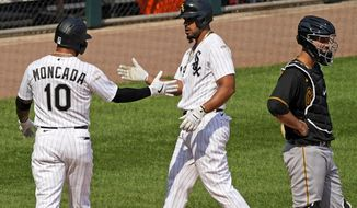 Chicago White Sox's Jose Abreu, center, celebrates with Yoan Moncada, left, after hitting a two-run home run as Pittsburgh Pirates catcher Jacob Stallings reacts during the seventh inning of a baseball game in Chicago, Wednesday, Aug. 26, 2020. (AP Photo/Nam Y. Huh)
