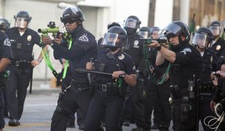 FILE - In this May 30, 2020, file photo, police aim weapons on a demonstrators protesting the death of George Floyd in Los Angeles. One of the hallmark bills of California lawmakers' policing reform efforts after months of nationwide social unrest cleared a hurdle Wednesday, Aug. 26, 2020, but faces tough going as the Legislature races to adjourn for the year on Monday, Aug. 31. (AP Photo/Ringo H.W. Chiu, File)